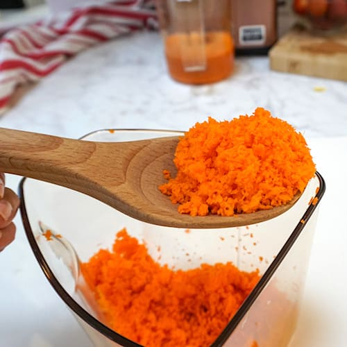 fine powdery carrot pulp on a wooden spoon
