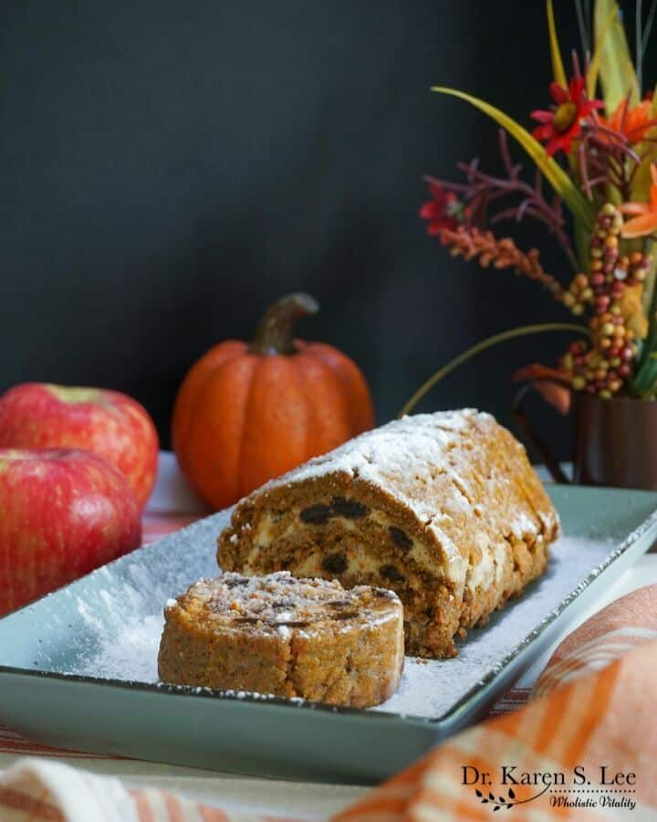 carrot pumpkin roll cake with a slice facing up on a blue rectangular plate with fall decoration around it
