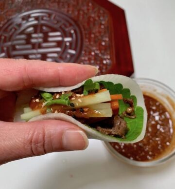 Two fingers holding a white radish wrap filled with colorful vegetables and bulgogi with brown sauce on top
