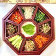 Colorful platter of nine vegetables in an octagonal wooden Korean dish