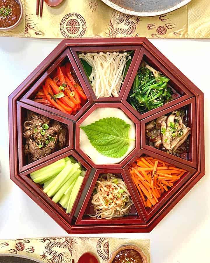 Colorful platter of nine vegetables in an octagonal wooden Korean dish