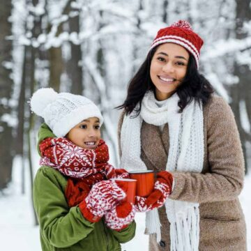 Smiling woman and child wearing winter outerwear outdoors