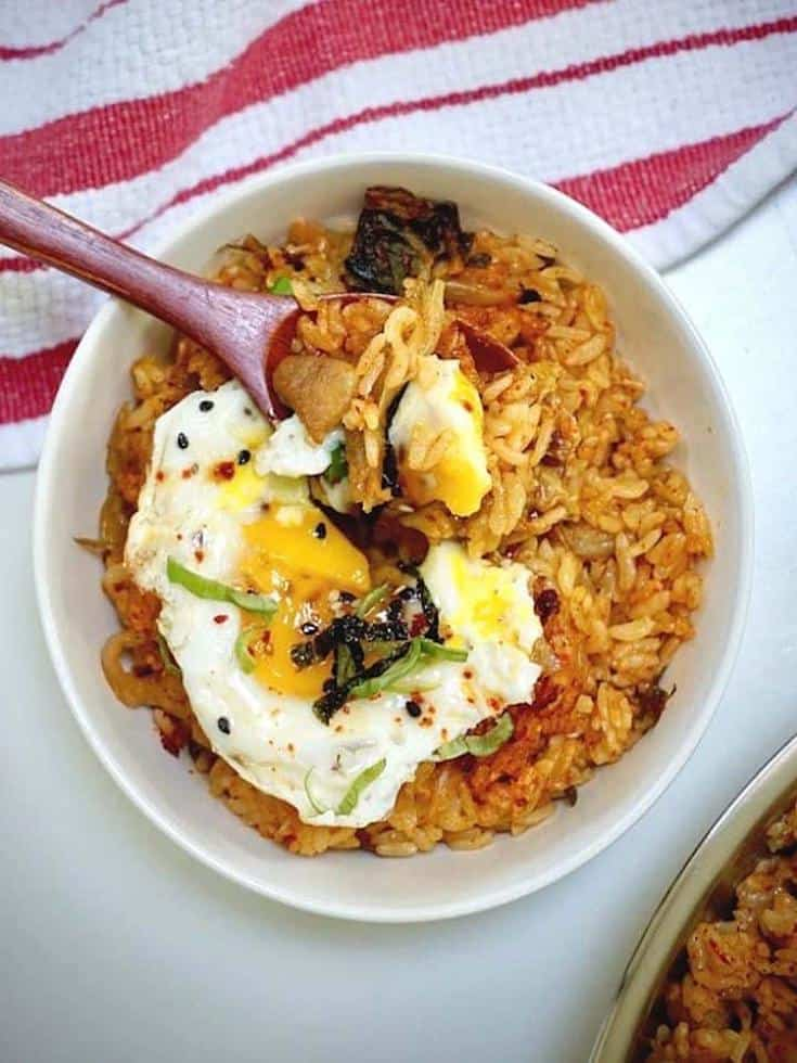 spoonful of kimchi pork fried rice with sunny side up egg on top above a white bowl filled the same on the table with red and white kitchen towel on it