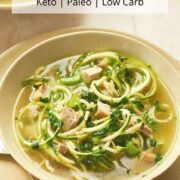 chicken zoodle soup in beige soup bowl on platter with a spoon