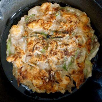Browned seafood pancake on a cast iron pan