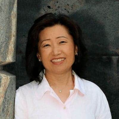 Smiling dark haired asian Woman in pink shirt