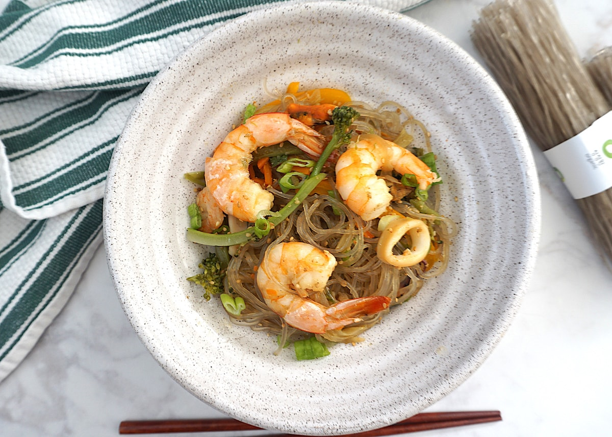 Light beige bowl with glass noodles with seafood and vegetables next to green white striped towel with brown chopsticks on right side