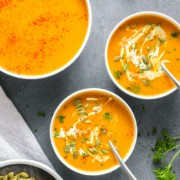 3 bowls of squash soup against grey background