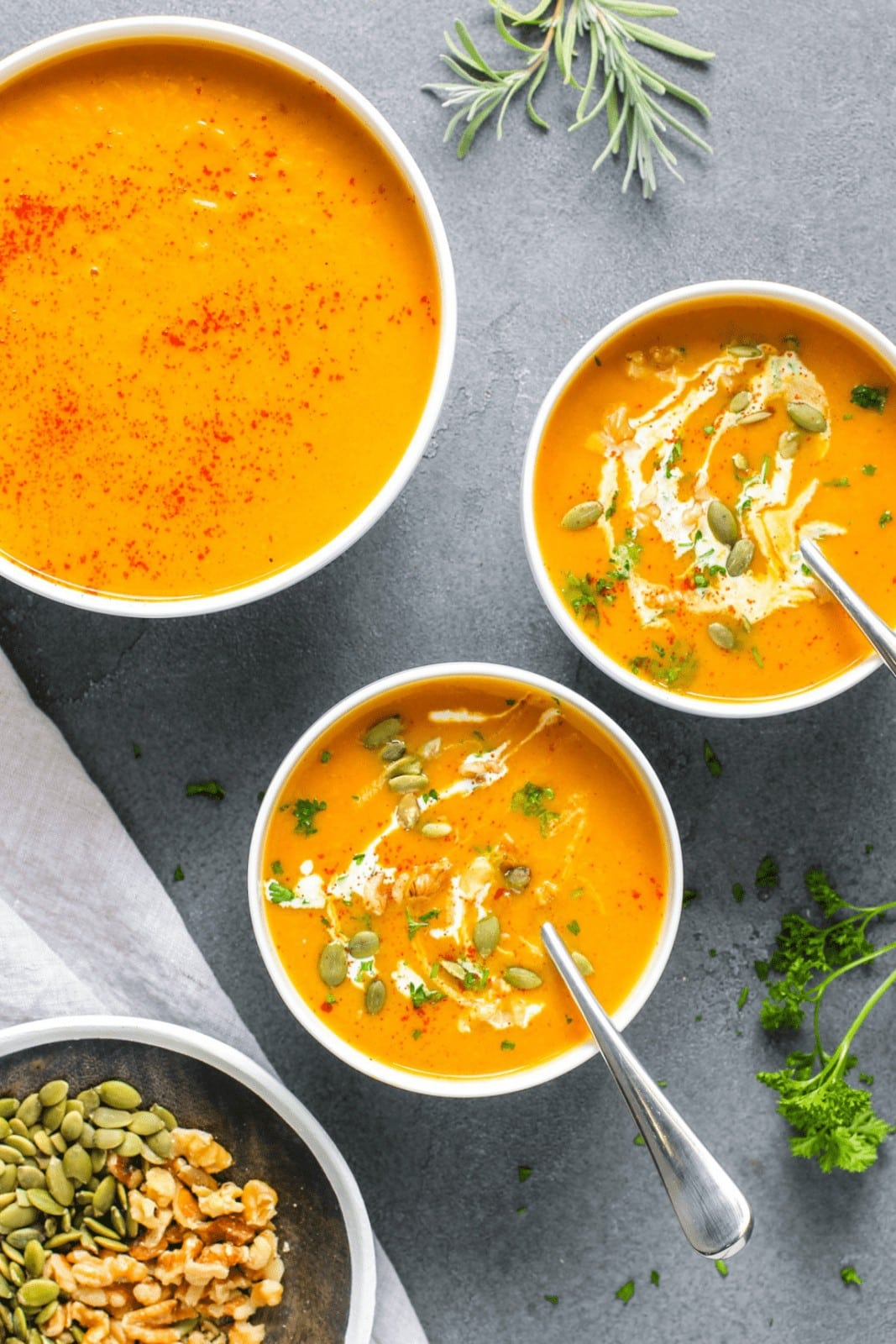 3 bowls of orange colored squash soup with cream and green garnish on grey background
