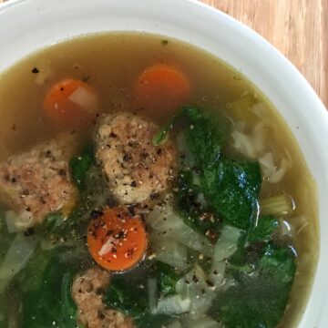 meatballs, carrots, green vegetable soup in white bowl